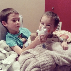 Caid helping out little bro Ian with  breathing treatment